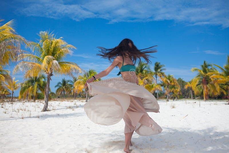Jovem mulher no roupa de banho e na saia de fluxo, dançando em uma praia das caraíbas fotografia de stock