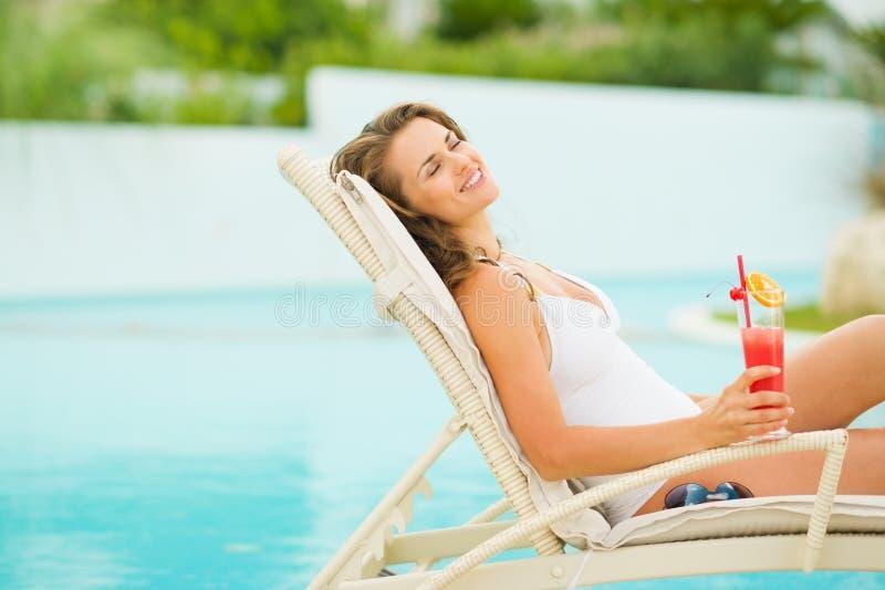 Jovem mulher no roupa de banho que relaxa com cocktail fotos de stock