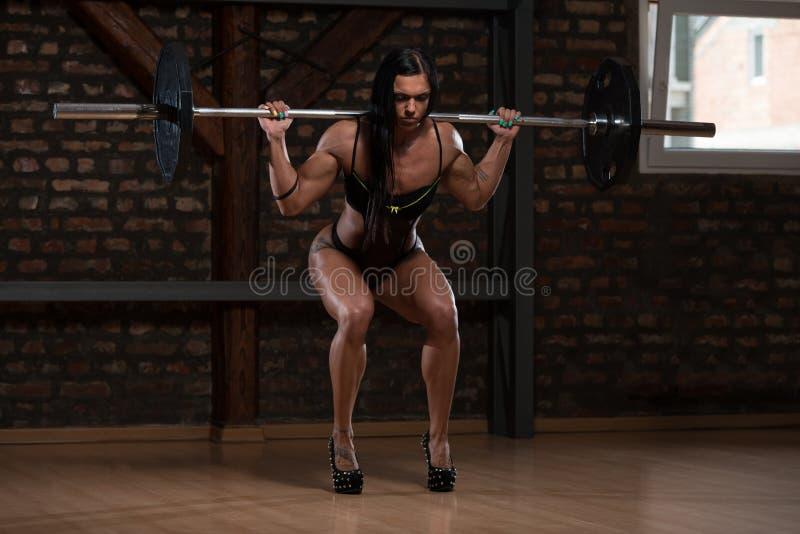 Jovem mulher no roupa interior que exercita a ocupa do Barbell imagem de stock