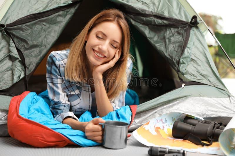 Jovem mulher no saco-cama com a caneca que olha fora imagens de stock royalty free