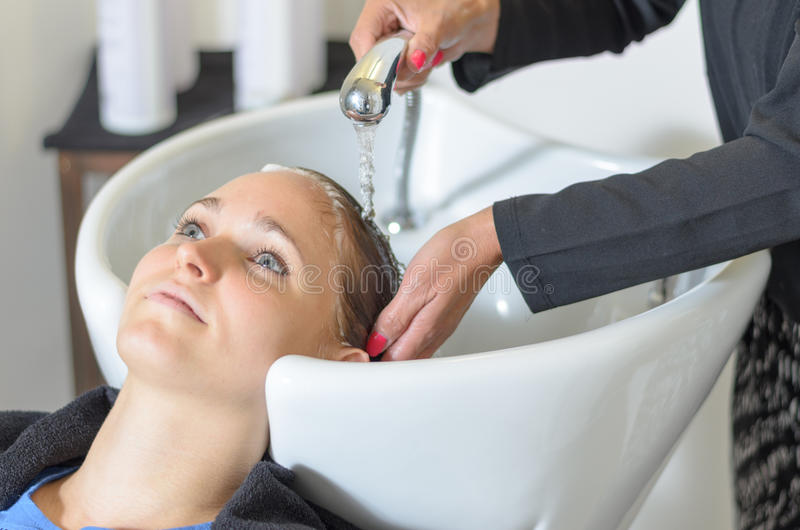 Jovem mulher no salão de beleza do cabeleireiro foto de stock