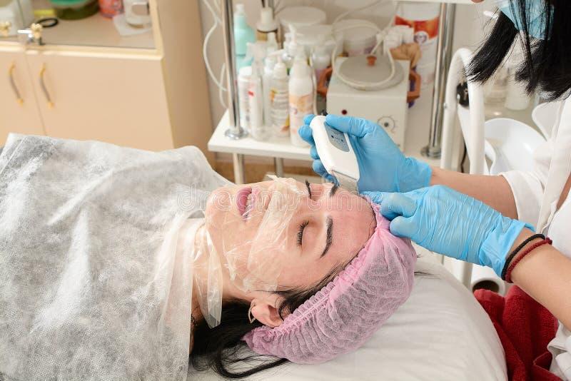 Jovem mulher no sal?o de beleza que faz a casca do ultrassom e o procedimento de limpeza facial fotos de stock royalty free