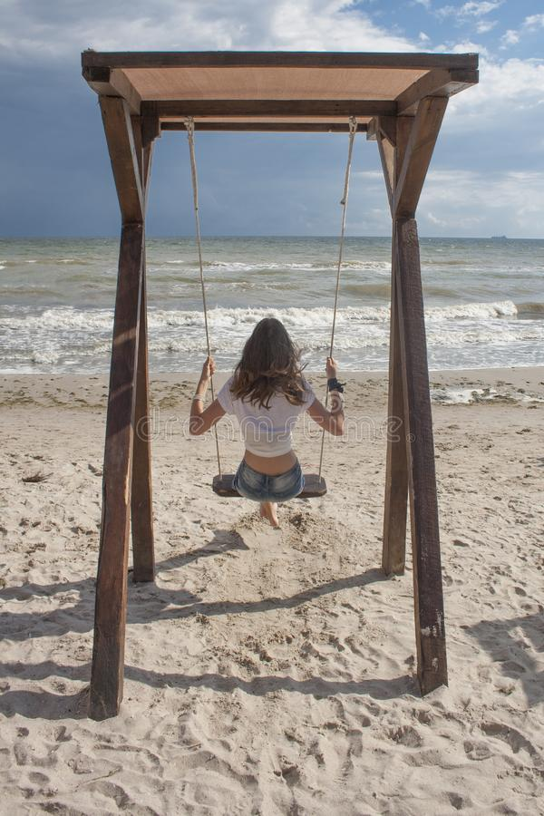 Jovem mulher no short da sarja de Nimes e no t-shirt branco que balançam em um balanço pelo mar imagem de stock