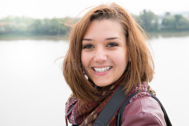 jovem mulher no sorriso do inverno e feliz no rio da cidade fotos de stock