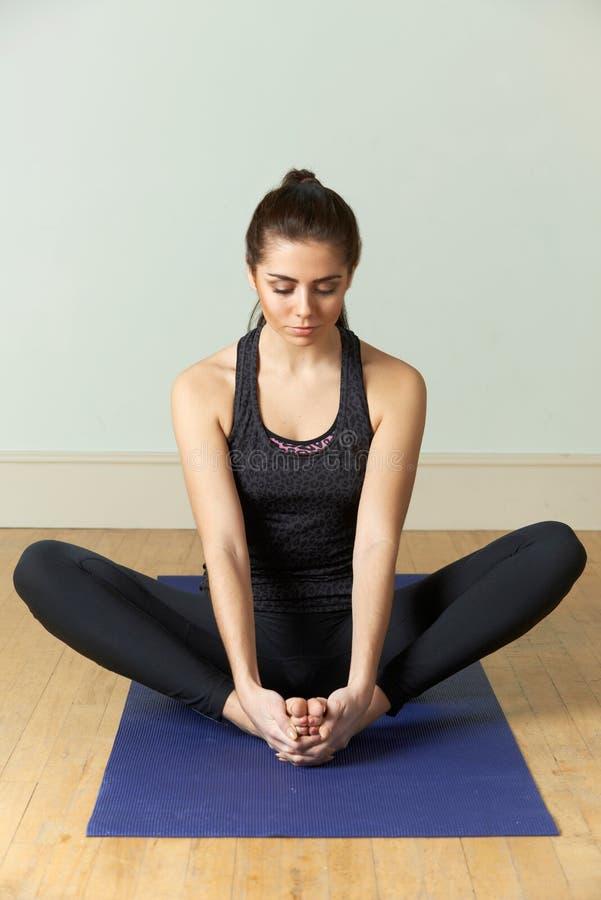 Jovem mulher no Sportswear que medita sobre a esteira foto de stock