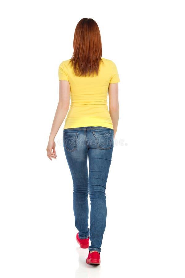 A jovem mulher no t-shirt amarelo, nas calças de brim e nas sapatilhas vermelhas está andando Vista traseira fotografia de stock