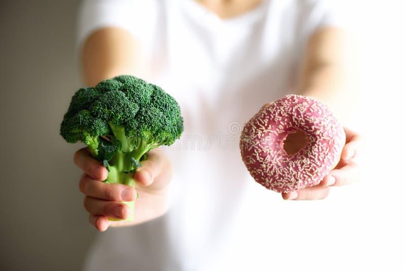 Jovem mulher no t-shirt branco que escolhe entre brócolis ou comida lixo, filhós Conceito limpo saudável comer da desintoxicação fotos de stock
