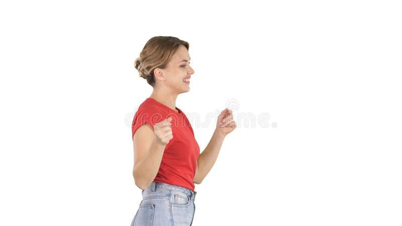 Jovem mulher no t-shirt vermelho, calças de brim que dançam e que andam no fundo branco imagens de stock