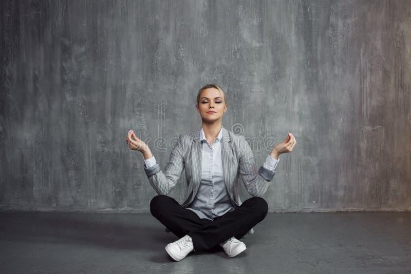 A jovem mulher no terno de negócio que senta-se na pose de Lotus, energia da restauração, medita Saúde e trabalho fotos de stock royalty free