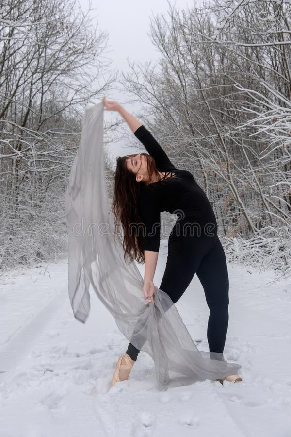 A jovem mulher no terno preto do bailado joga na floresta nevado com um pano brilhante fotografia de stock