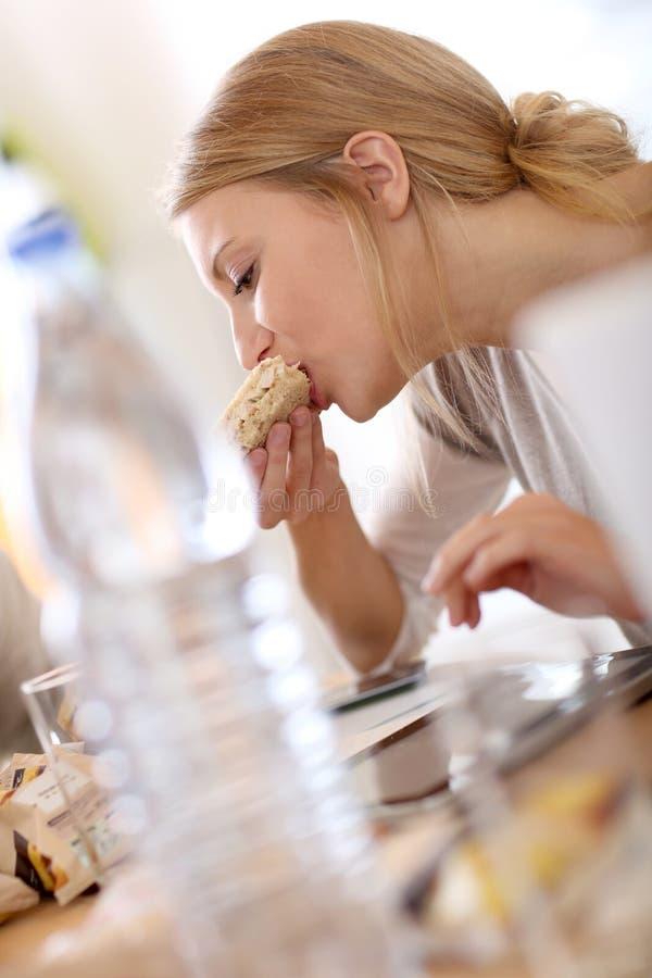 Jovem mulher no trabalho que come o petisco e que usa a tabuleta imagens de stock royalty free