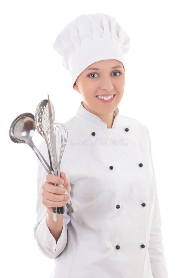 Jovem mulher no uniforme do cozinheiro chefe com o equipamento da cozinha isolado em w fotos de stock