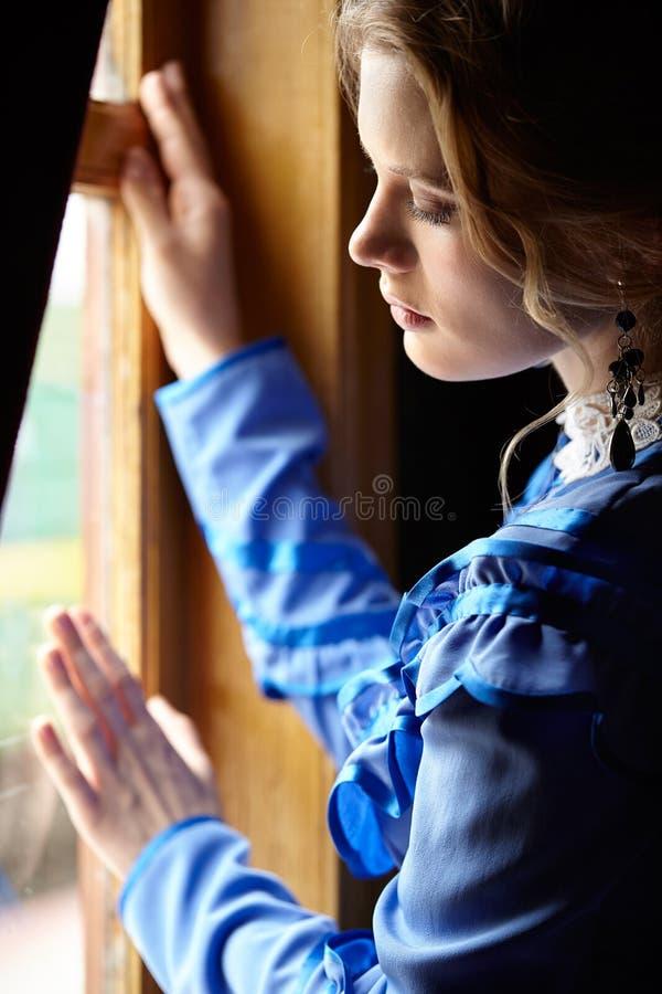 Jovem mulher no vestido azul do vintage que está a janela próxima no cupê fotografia de stock