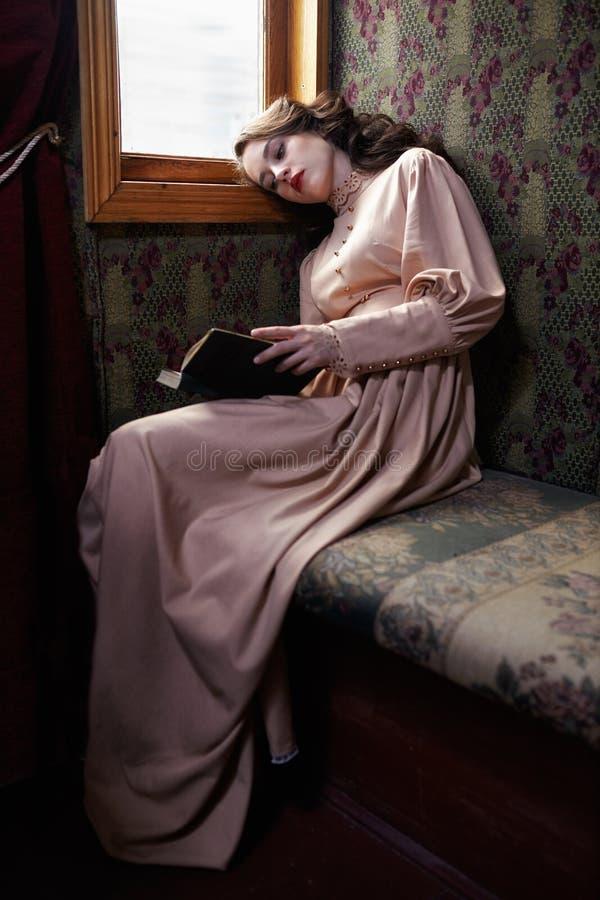 Jovem mulher no vestido bege do vintage da leitura do início do século XX imagens de stock