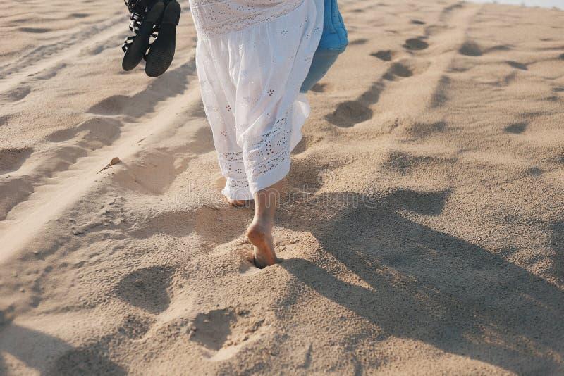 Jovem mulher no vestido branco que anda apenas na praia fotografia de stock royalty free