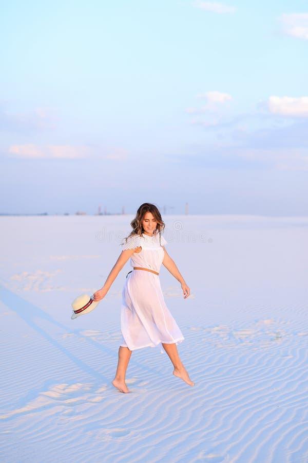 Jovem mulher no vestido branco que anda na areia e que mantém o chapéu fotografia de stock