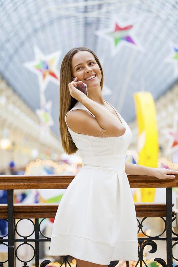 Jovem mulher no vestido branco que chama um telefone celular foto de stock