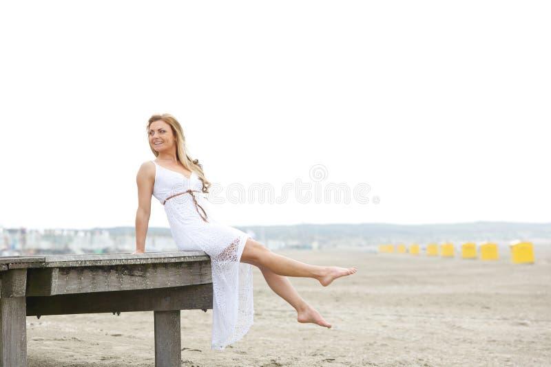 Jovem mulher no vestido branco que senta-se na praia fotografia de stock