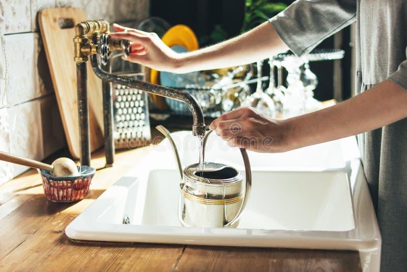 A jovem mulher no vestido cinzento derrama a água na chaleira na cozinha, rotina da manhã foto de stock