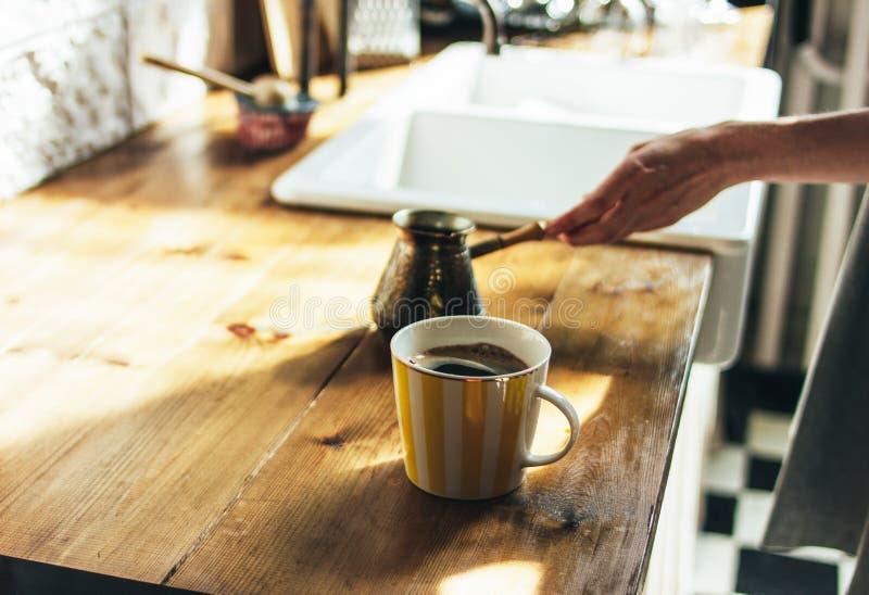 A jovem mulher no vestido cinzento derrama o café fresco natural em uma caneca na cozinha, manhã, luz dura fotografia de stock