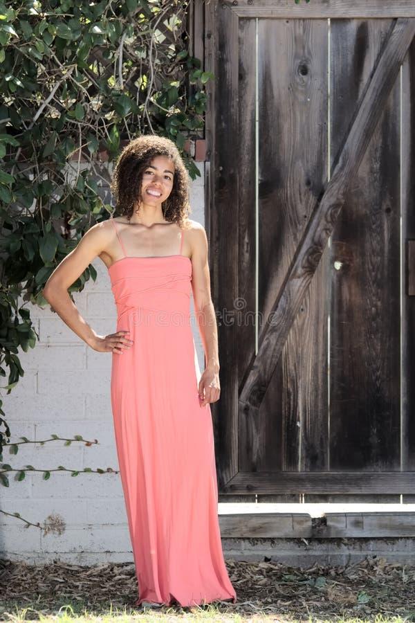 Jovem mulher no vestido cor-de-rosa com mão no quadril fotografia de stock