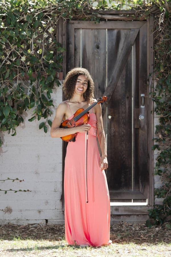 Jovem mulher no vestido cor-de-rosa que guarda o violino fora imagens de stock royalty free