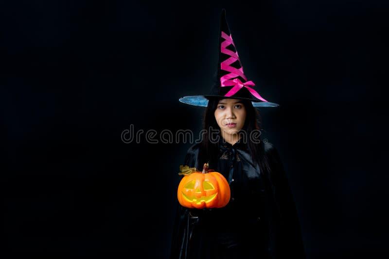 Jovem mulher no vestido da bruxa que guarda o vidro de vinho, tiro do estúdio no bl imagem de stock royalty free
