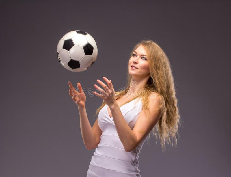 Jovem mulher no vestido de noite branco com bola de futebol fotos de stock royalty free