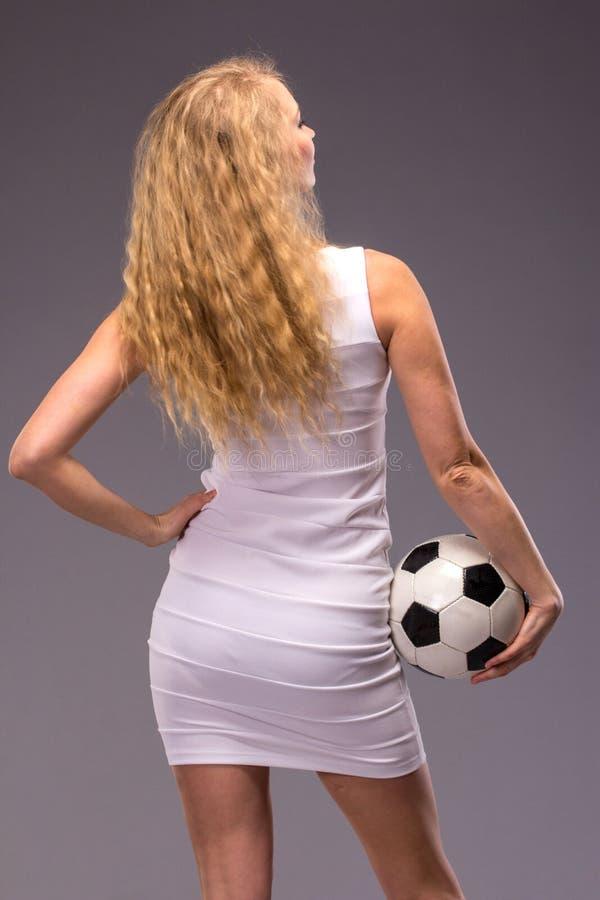 Jovem mulher no vestido de noite branco com bola de futebol foto de stock royalty free
