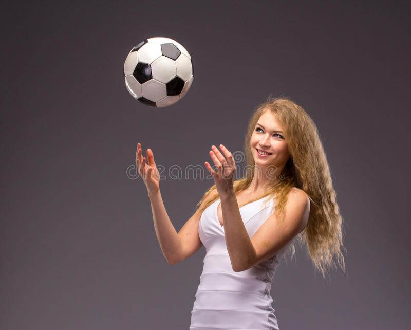 Jovem mulher no vestido de noite branco com bola de futebol fotografia de stock royalty free