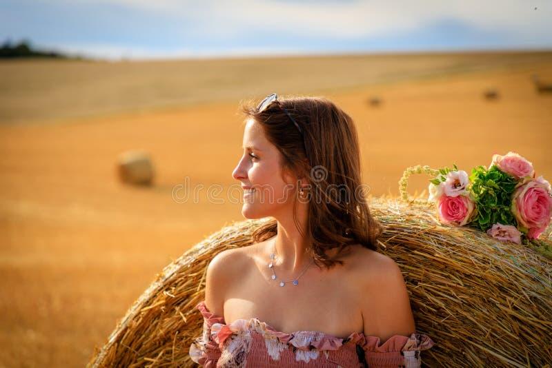 A jovem mulher no vestido do verão inclina-se contra um pacote da palha foto de stock