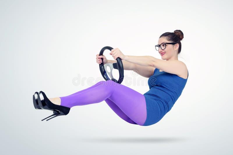 Jovem mulher no vestido e em vidros azuis com um volante do carro Conceito do motorista da senhora foto de stock