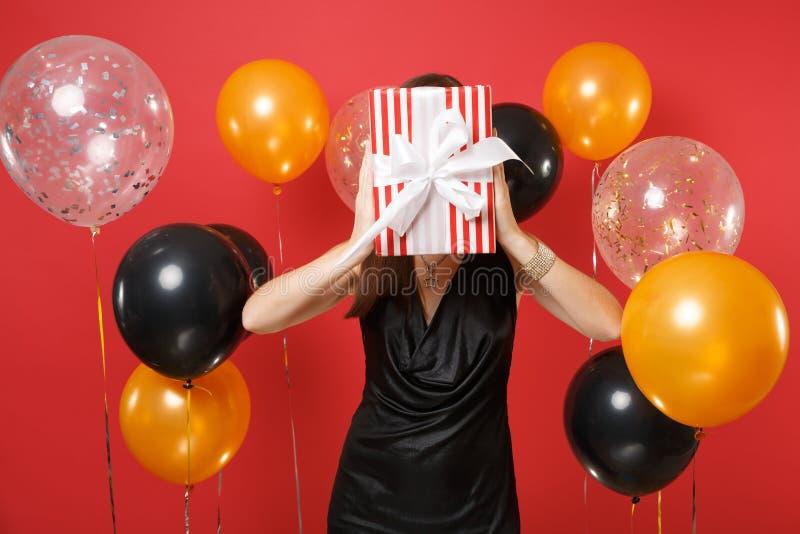 A jovem mulher no vestido preto pequeno que comemora, cobrindo a cara e escondendo atrás da caixa vermelha com presente, apresent fotos de stock royalty free