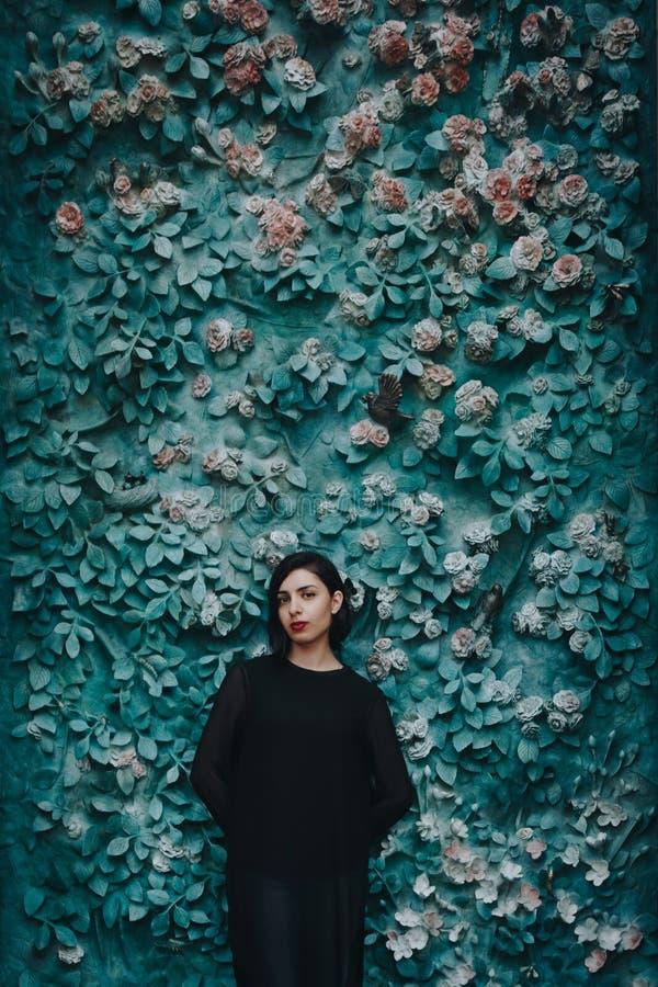 Jovem mulher no vestido preto perto da parede verde com flores foto de stock royalty free