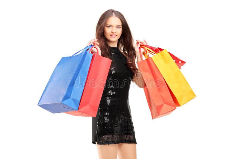 Jovem mulher no vestido preto que guardara sacos de compras foto de stock royalty free