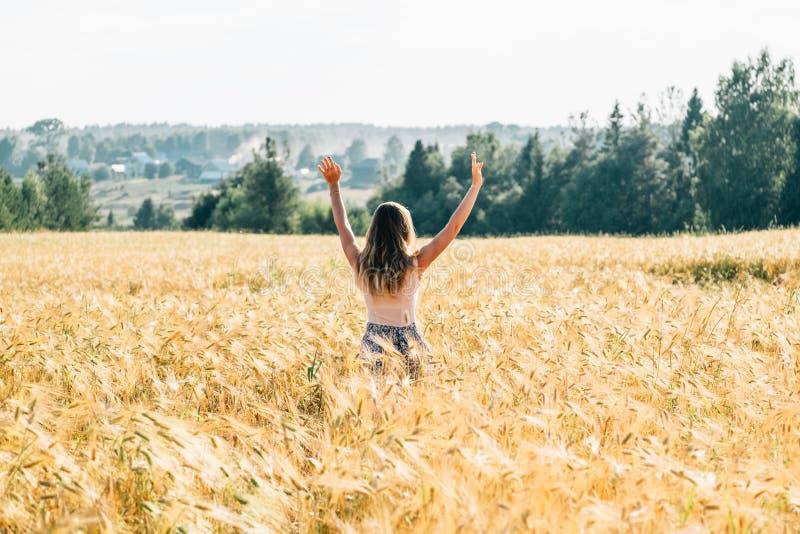 Jovem mulher no vestido que anda ao longo do campo de cereal fotos de stock