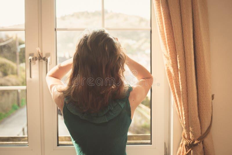 Jovem mulher no vestido que olha para fora a janela fotografia de stock royalty free