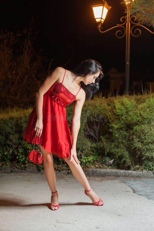 Jovem mulher no vestido sem mangas vermelho que anda no parque da noite fotografia de stock