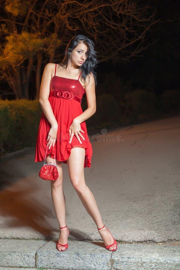 Jovem mulher no vestido sem mangas vermelho que anda no parque da noite fotos de stock royalty free