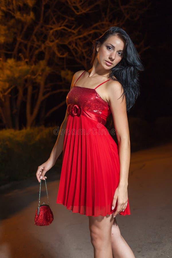 Jovem mulher no vestido sem mangas vermelho que anda no parque da noite imagem de stock royalty free