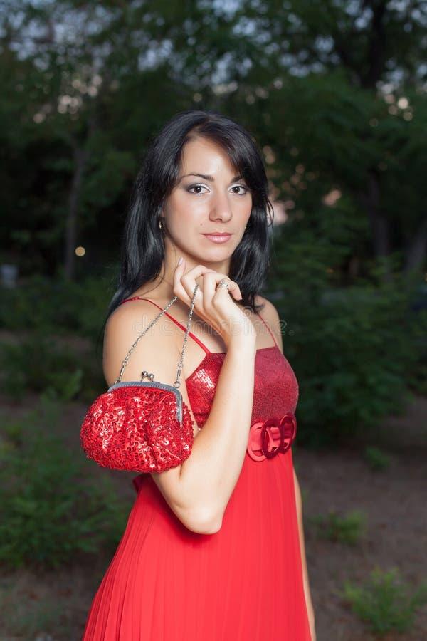 Jovem mulher no vestido sem mangas vermelho que levanta no parque da noite imagens de stock royalty free