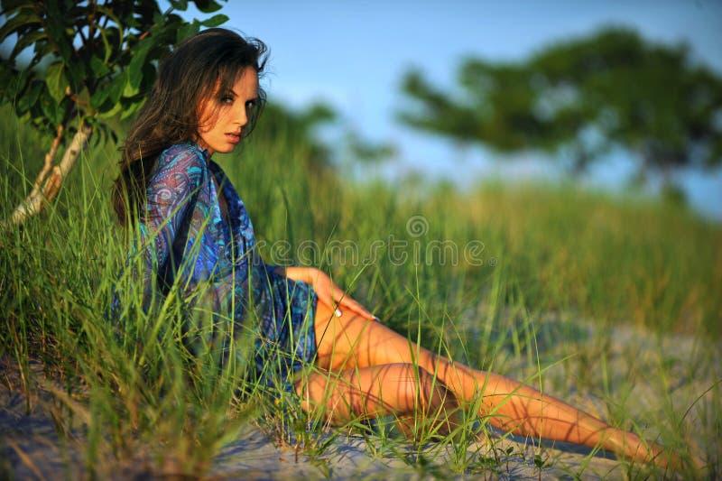 Jovem mulher no vestido transparente floral que levanta consideravelmente na praia imagem de stock