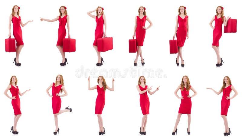 A jovem mulher no vestido vermelho com a mala de viagem isolada no branco imagem de stock