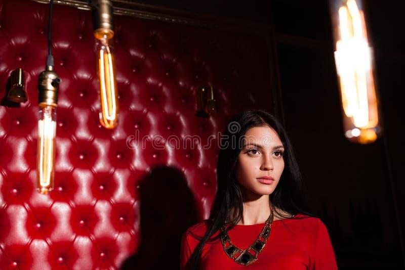 Jovem mulher no vestido vermelho que está a parede próxima foto de stock royalty free