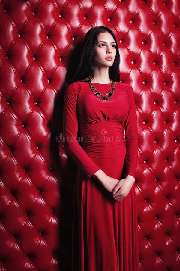 Jovem mulher no vestido vermelho que está a parede próxima imagem de stock
