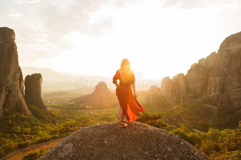 Jovem mulher no vestido vermelho que olha o por do sol majestoso no vale de Meteora, Grécia imagens de stock royalty free