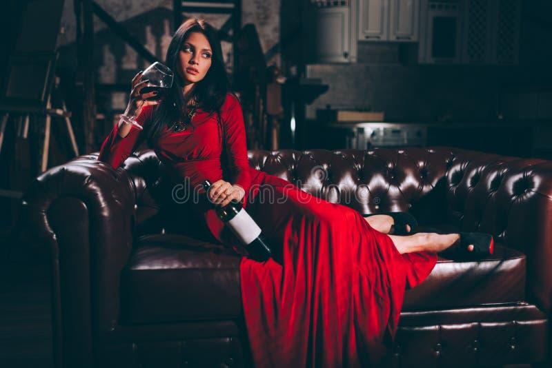 Jovem mulher no vestido vermelho que senta-se no sofá de couro imagens de stock royalty free