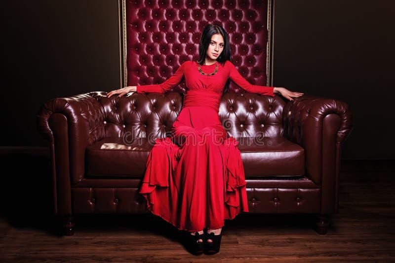 Jovem mulher no vestido vermelho que senta-se no sofá de couro foto de stock royalty free