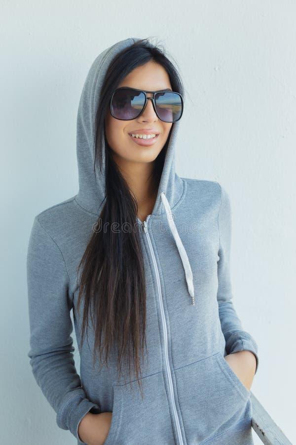 Jovem mulher nos óculos de sol e no hoodie cinzento imagens de stock