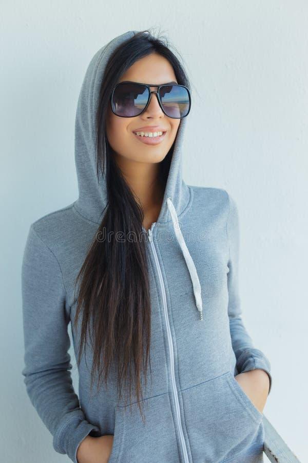 Jovem mulher nos óculos de sol e no hoodie cinzento foto de stock royalty free